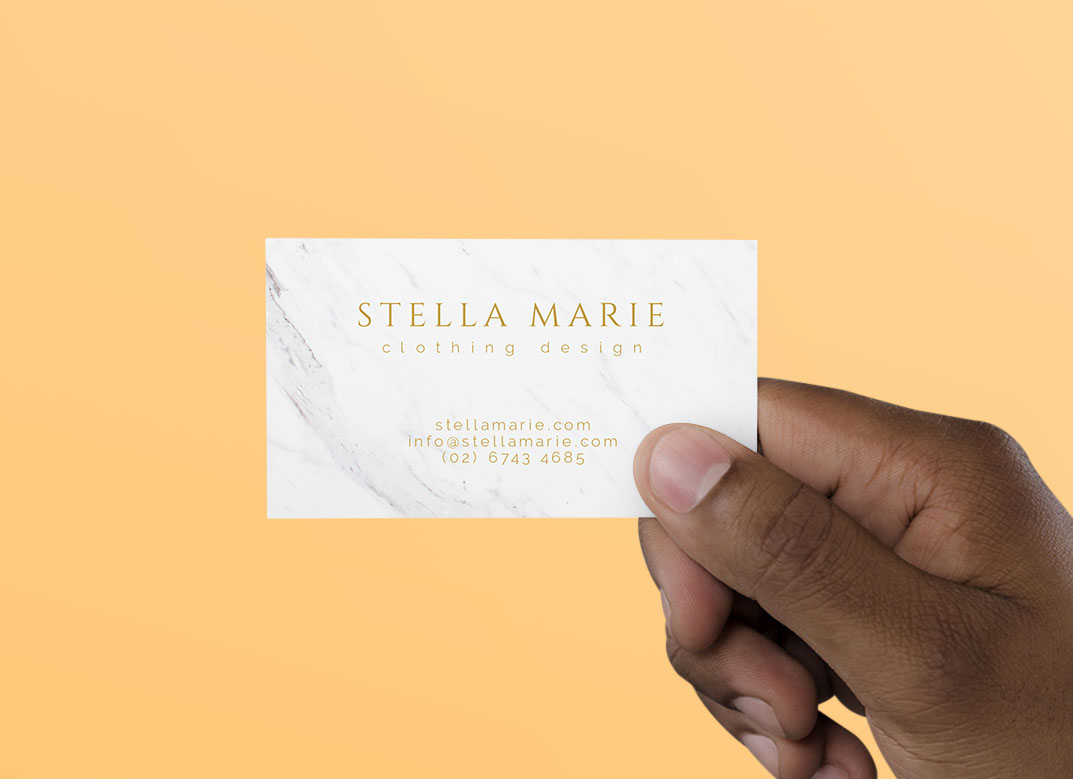 A hand is holding a printed white marble Business Cards Templates with orange background